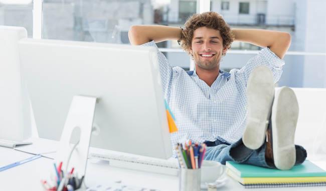 Jeune homme devant un ordinateur qui a les pieds sur son bureau
